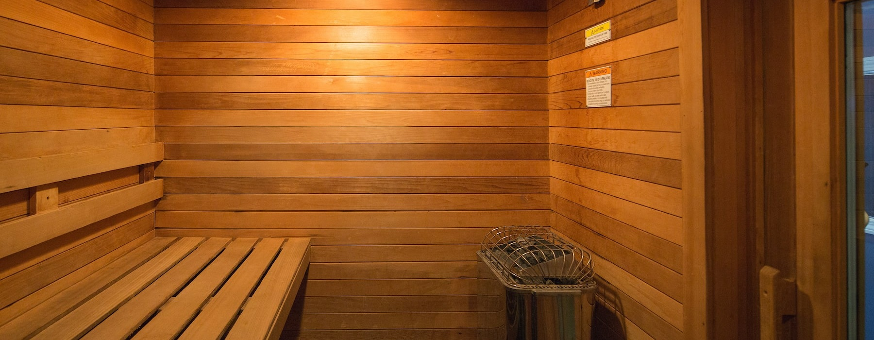 well lit wood sauna with seating bench and steamer